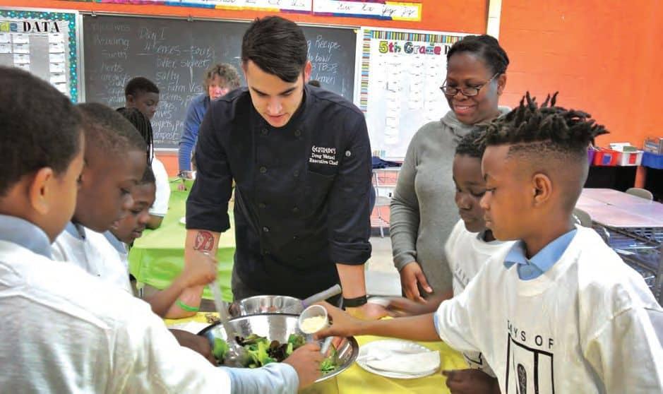TasteWise kids mix a salad with Doug Wetzel, chef at Gertrude's restaurant.